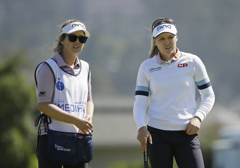 Brooke Henderson, right, of Canada, and her caddie and sister, Brittany Henderson, look over the ninth green of the Lake Merced Golf Club during the first round of the LPGA Mediheal Championship golf tournament Thursday, May 2, 2019, in Daly City, Calif. (AP Photo/Eric Risberg)