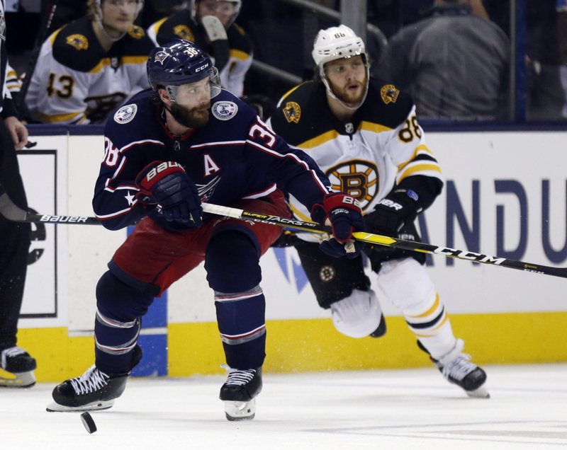 Columbus Blue Jackets forward Boone Jenner, left, chases the puck next to Boston Bruins forward David Pastrnak, of the Czech Republic, during the second period of Game 4 of an NHL hockey second-round playoff series in Columbus, Ohio, Thursday, May 2, 2019. (AP Photo/Paul Vernon)