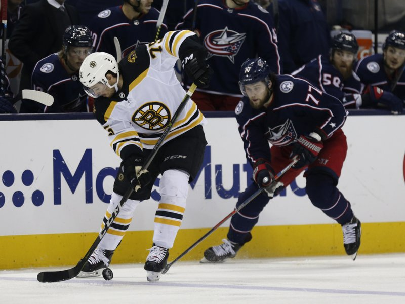 Boston Bruins defenseman Connor Clifton, left, settles the puck as Columbus Blue Jackets forward Josh Anderson defends during the second period of Game 4 of an NHL hockey second-round playoff series in Columbus, Ohio, Thursday, May 2, 2019. (AP Photo/Paul Vernon)