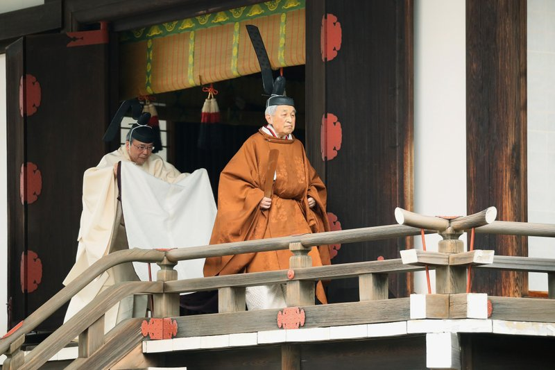 In this April 30, 2019, photo, Japan's Emperor Akihito, right, leaves after a ritual to report his abdication to the throne, at the Imperial Palace in Tokyo. The 85-year-old Akihito ends his three-decade reign on Tuesday when he abdicates to his son Crown Prince Naruhito. (Japan Pool via AP)