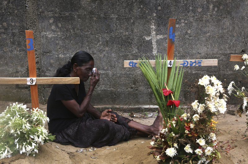 In this April 28, 2019, photo,  a relative of a victim of Easter bomb blasts wipes her tears during a prayer at the burial site of her relatives after a televised Sunday mass by Sri Lankan Archbishop Cardinal Malcolm Ranjith, in Negombo, north of Colombo, Sri Lanka. Sri Lanka's Catholics celebrated Sunday Mass in their homes by a televised broadcast as churches across the island nation shut over fears of militant attacks, a week after the Islamic State-claimed Easter suicide bombings killed over 250 people. (AP Photo/Manish Swarup)