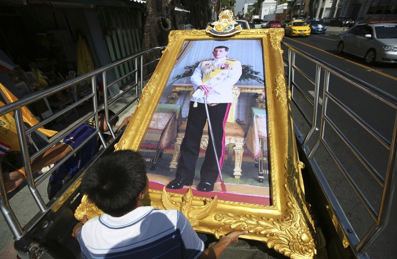 In this April 29, 2019, photo, Thai workers prepare to transport a giant portrait of Thailand's King Maha Vajiralongkorn by truck to a buyer's house in Bangkok, Thailand. The coronation ceremonies for 66-year-old King Maha Vajiralongkorn, also known as King Rama X, will be held on May 4-6, 2019. (AP Photo/Sakchai Lalit)