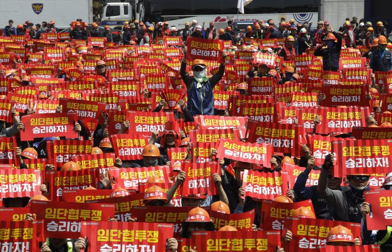 In this May 1, 2019, photo, members of the Korean Confederation of Trade Unions hold up their banners during a May Day rally in Seoul, South Korea. Thousands of trade union members and activists are marking May Day by marching through Asia's capitals and demanding better working conditions and expanding labor rights. The signs read