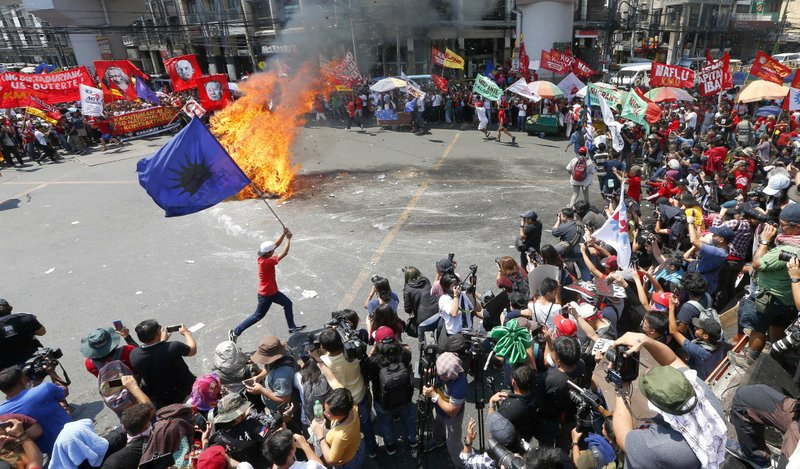 In this May 1, 2019, photo,  a protester runs around a burning effigy of President Rodrigo Duterte during a rally near the Presidential Palace in Manila, Philippines, to pay tribute to workers in celebration of International Labor Day. The workers scored Duterte allegedly for reneging in his campaign promise three years ago to end temporary hiring known as