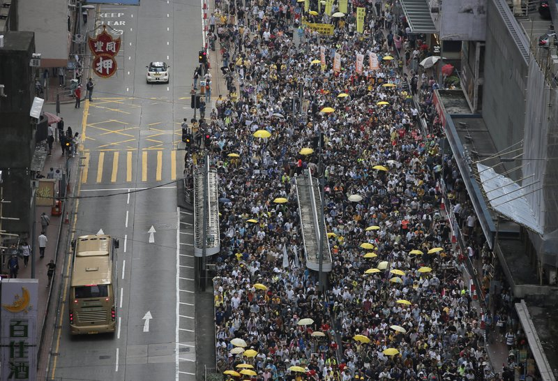 In this April 28, 2019, photo, protesters against an extradition law march along a downtown street in Hong Kong. Thousands of people protested to express their concerns about the proposed new extradition law that would make it possible for people to be sent to mainland China to face the justice system there. (AP Photo/Vincent Yu)