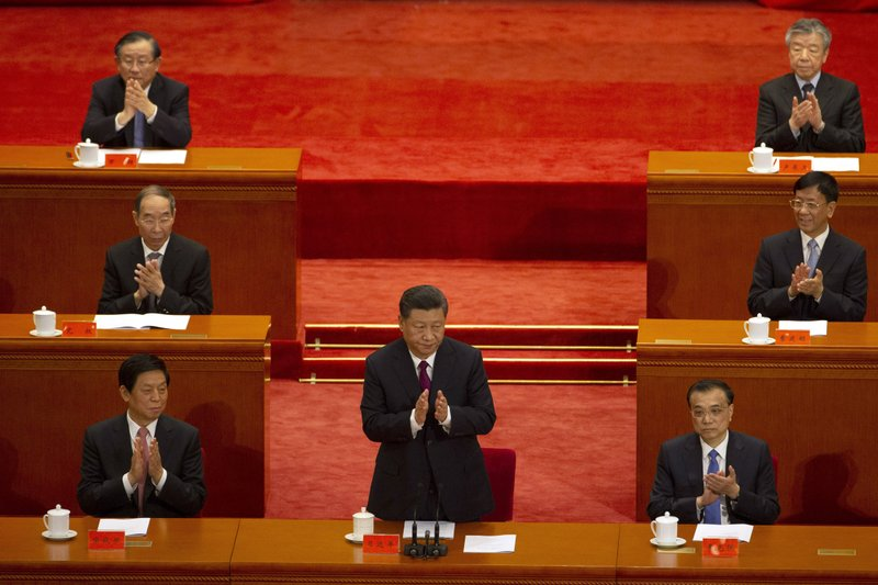 In this April 30, 2019, photo, Chinese President Xi Jinping, center, applauds as he attends a commemoration ahead of the 100th anniversary of the May 4 Movement at the Great Hall of the People in Beijing. The 100-year-old movement sought to overturn what was then called