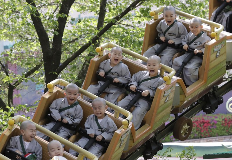 In this May 2, 2019, photo, Shaven-headed children ride a roller coaster during their visit at the Everland amusement park in Yongin, South Korea. Ten children entered a temple to have an experience of monks' life for three weeks. Buddhists visit a temple across the country to celebrate the Buddha's upcoming birthday on May 12. (AP Photo/Lee Jin-man)