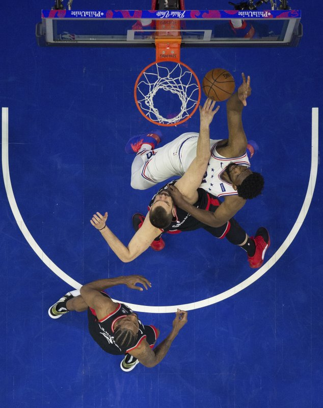 Philadelphia 76ers' Joel Embiid, right, shoots against Toronto Raptors' Marc Gasol, center, with Kawhi Leonard, left, watching during the first half of Game 3 of a second-round NBA basketball playoff series, Thursday, May 2, 2019, in Philadelphia. (AP Photo/Chris Szagola)