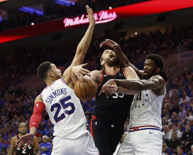 Toronto Raptors' Marc Gasol, center, is fouled by Philadelphia 76ers' Ben Simmons, left, with Joel Embiid, right, also defending during the first half of Game 3 of a second-round NBA basketball playoff series, Thursday, May 2, 2019, in Philadelphia. (AP Photo/Chris Szagola)