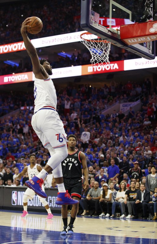 Philadelphia 76ers' Joel Embiid goes up for the dunk as Toronto Raptors' Kyle Lowry watches during the second half of Game 3 of a second-round NBA basketball playoff series Thursday, May 2, 2019, in Philadelphia. The 76ers won 116-95. (AP Photo/Chris Szagola)
