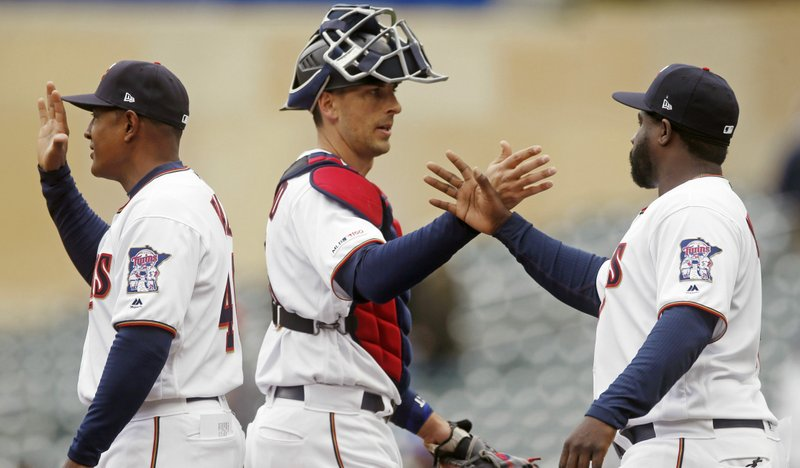 Minnesota Twins' Jason Castro, center, goes through the celebration line after the Twins beat the Houston Astros 8-2 in a baseball game Thursday, May 2, 2019, in Minneapolis. Castro had four RBIs, including a home run. (AP Photo/Jim Mone)