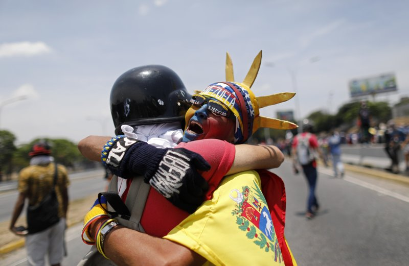 An anti-government protester dressed as Lady Liberty, wearing the colors of Venezuela's flag, hugs a fellow protester during a demonstration near La Carlota airbase in Caracas, Venezuela, Wednesday, May 1, 2019. Opposition leader Juan Guaidó is calling for Venezuelans to fill streets around the country Wednesday to demand President Nicolás Maduro's ouster. Maduro is also calling for his supporters to rally. (AP Photo/Ariana Cubillos)