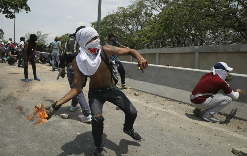 An anti-government protester launches a molotov cocktail at National Guard forces outside La Carlota airbase during clashes between the two sides in Caracas, Venezuela, Wednesday, May 1, 2019. Opposition leader Juan Guaido called for Venezuelans to fill streets around the country Wednesday to demand President Nicolas Maduro's ouster. Maduro is also calling for his supporters to rally. (AP Photo/Rodrigo Abd)