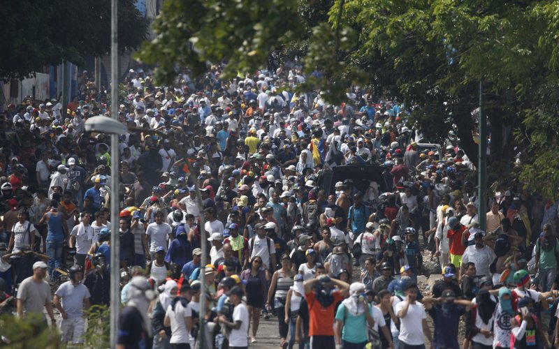 Anti-government protesters fill a street during clashes with security forces near La Carlota airbase in Caracas, Venezuela, Wednesday, May 1, 2019. Opposition leader Juan Guaidó called for Venezuelans to fill streets around the country Wednesday to demand President Nicolás Maduro's ouster. (AP Photo/Ariana Cubillos)