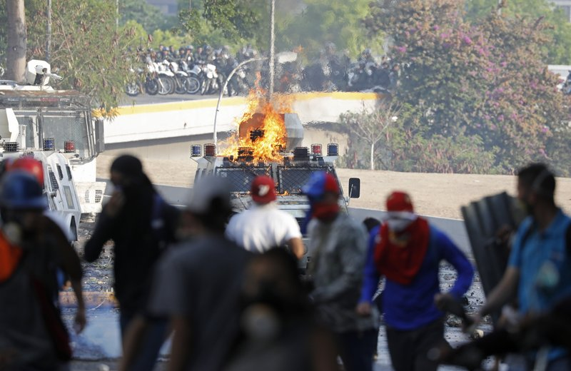 A security forces armed vehicle burns after it was set on fire by anti-government protesters, front, near La Carlota airbase in Caracas, Venezuela, Wednesday, May 1, 2019. Opposition leader Juan Guaidó called for Venezuelans to fill streets around the country Wednesday to demand President Nicolás Maduro's ouster. (AP Photo/Ariana Cubillos)