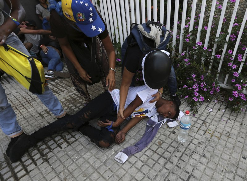 An anti-government protester who collapsed after being overcome by teargas is helped by fellow demonstrators during clashes with security forces, in Caracas, Venezuela, Wednesday, May 1, 2019. Opposition leader Juan Guaidó called for Venezuelans to fill streets around the country Wednesday to demand President Nicolás Maduro's ouster. Maduro is also calling for his supporters to rally. (AP Photo/Fernando Llano)