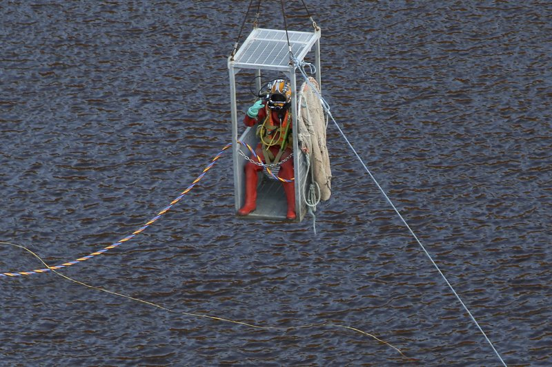 A diver is lowered into a man-made lake to search for suitcases containing the bodies of three murdered victims, near the village of Mitsero outside of the capital Nicosia, Cyprus, Thursday, May 2, 2019. The justice minister in Cyprus resigned amid mounting criticism that police bungled their investigations when some of the seven foreign women and girls slain by a serial killer were initially reported missing. (AP Photo/Petros Karadjias)