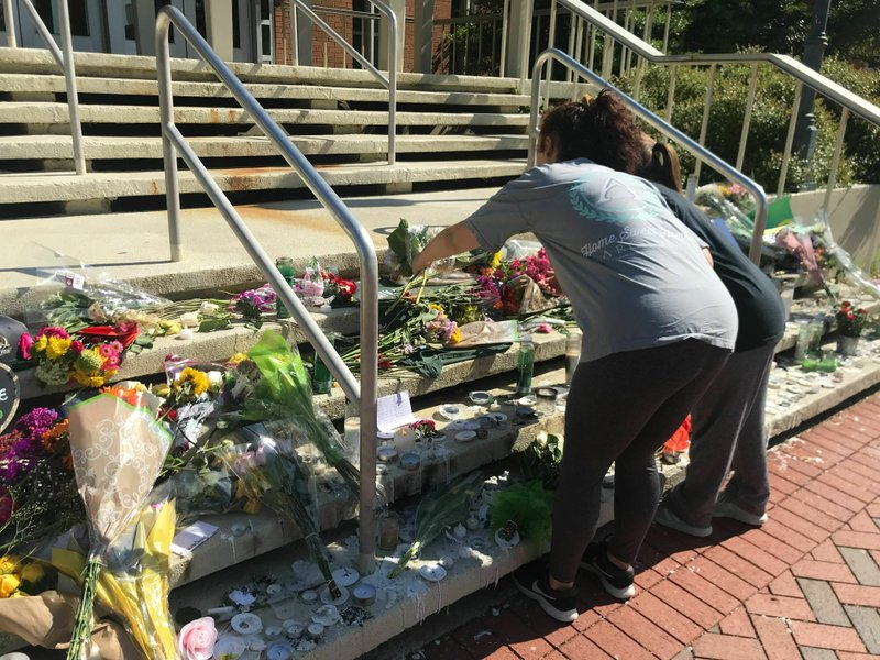 Mourners pause to look at a variety of memorials left at Kennedy Hall at the University of North Carolina at Charlotte on Thursday, May 2, 2019. A gunman opened fire at Kennedy on Tuesday, killing two and wounding four. (AP Photo/Sarah Blake Morgan)