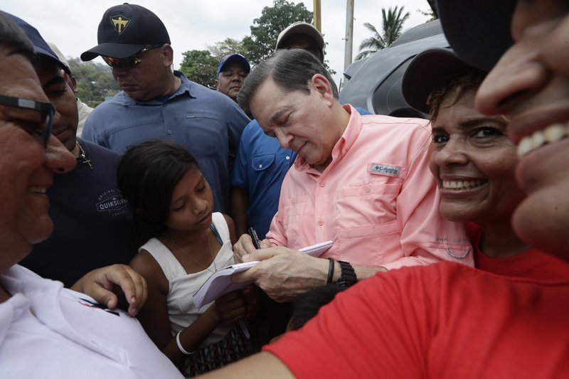 In this April 14, 2019 photo, leading presidential candidate Laurentino Cortizo, of the Democratic Revolutionary Party, signs autographs after a campaign rally in Veracruz, Panama. A recent poll by La Prensa newspaper gave Cortizo, a 66-year-old businessman with a degree in business administration from Norwich University in Vermont, a double-digit edge over his two nearest rivals. (AP Photo/Arnulfo Franco)