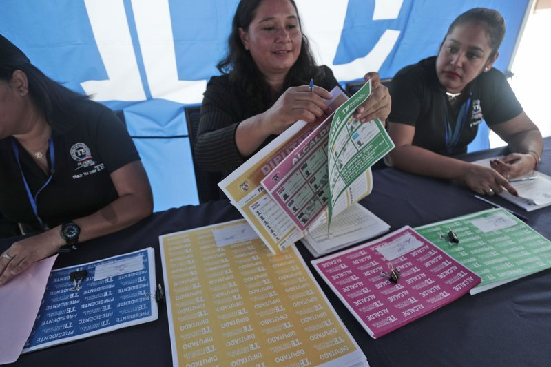 An electoral worker demonstrates how to properly handle ballots during a Voting Fair for citizens at the Electoral Tribunal headquarters in Panama City, Thursday, May 2, 2019. Panamanians head to the polls on Sunday, May 5, to elect a new president. (AP Photo/Arnulfo Franco)