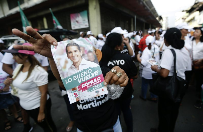 A supporter of Romulo Roux, presidential candidate of the Democratic Change Party, holds up a party leaflet during his closing campaign rally in Panama City, Thursday, May 2, 2019. Roux has tried to capitalize on economic unease. (AP Photo/Arnulfo Franco)