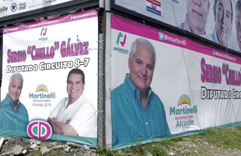 In this April 28, 2019 photo, a billboard promotes former President Ricardo Martinelli as a mayoral candidate for Panama City representing the Democratic Change party, in Panama City. Panama's electoral court ruled that the jailed ex-president may not participate in the May 5th general elections. Martinelli has been behind bars on charges of political espionage since being extradited from the U.S. last June. (AP Photo/Arnulfo Franco)