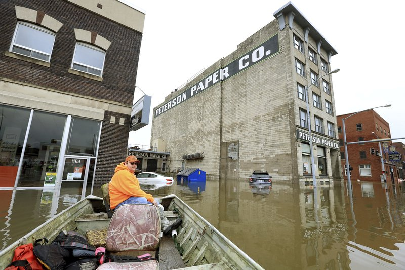 Ryan Lincoln maneuvers his boat through flood water at the intersection of Pershing Ave and E 2nd St. Thursday, May 2, 2019. Lincoln's employer Hahn Ready Mix allowed him to take time off from work to volunteer ferrying people back and forth to their apartments and businesses affected by the flooding in downtown Davenport. The Mississippi River is expected to reach a record level of 22.7 feet Thursday night. (Kevin E. Schmidt/Quad City Times via AP)