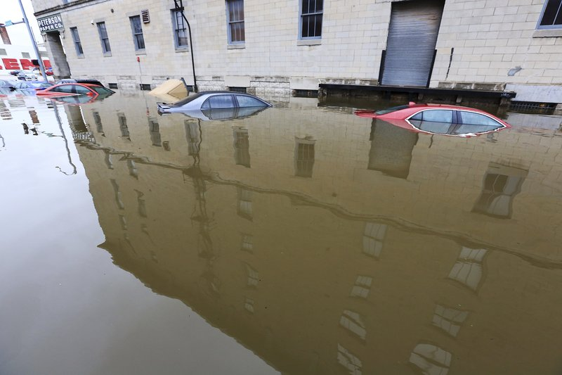 Vehicles sit in flood water next to the Peterson Paper Co. building on Pershing Ave in downtown Davenport, Thursday, May 2, 2019. The Mississippi River is expected to reach a record level of 22.7 feet Thursday night.  (Kevin E. Schmidt/Quad City Times via AP)