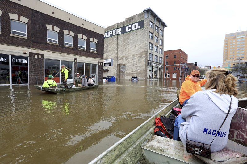 Ryan Lincoln maneuvers his boat through flood water while taking volunteer Donna Magnus to Dress for Success on E 2nd St. in downtown Davenport Thursday, May 2, 2019. The Mississippi River is expected to reach a record level of 22.7 feet Thursday night. (Kevin E. Schmidt/Quad City Times via AP)
