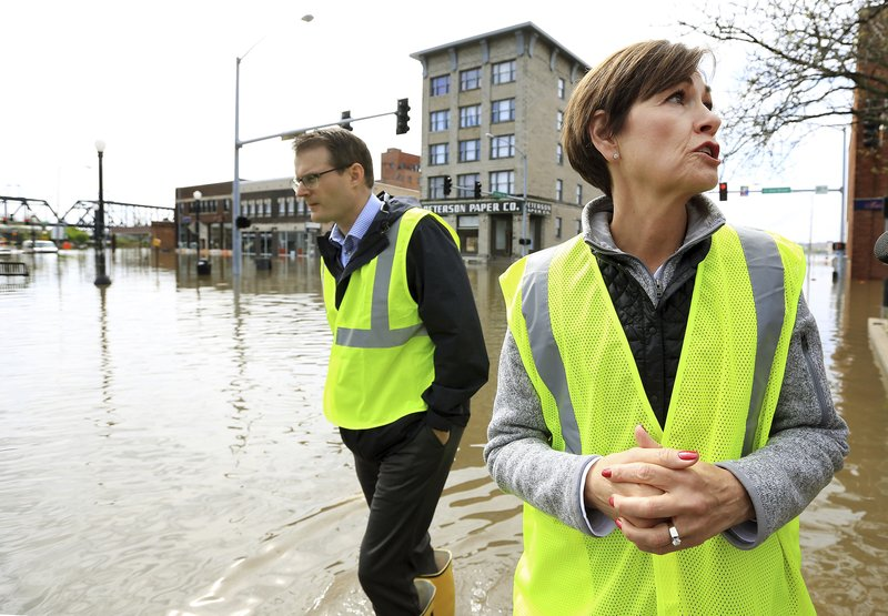 Iowa Gov. Kim Reynolds, right stops to talk with the media near the intersection of Pershing Ave. and E 2nd St. in downtown Davenport, Iowa during a tour of flooded areas of the community Friday, May 3, 2019. (Kevin E. Schmidt/Quad City Times via AP)