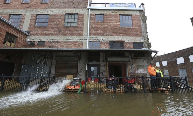 Workers stand near the back entrance of the 1/2 Nelson restaurant as pumps continue pumping flood water from the basement of the new Davenport business Thursday, May 2, 2019. The Mississippi River is expected to reach a record level of 22.7 feet Thursday night.  (Kevin E. Schmidt/Quad City Times via AP)
