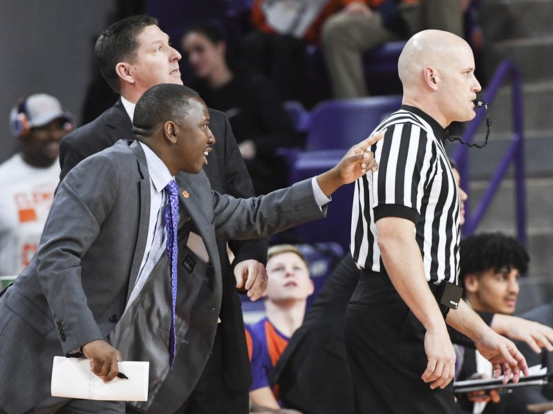 In this February, 2019 photo, Clemson assistant coach Steve Smith, left, gestures as head coach Brad Brownell, rear left, during an NCAA college basketball game in Clemson, S.C. Clemson has parted ways Smith on Friday, May 3, 2019, after his voice was heard on a federal wiretap involving defendant Christian Dawkins on the ongoing trial into college corruption. (Ken Ruinard/The Independent-Mail via AP)