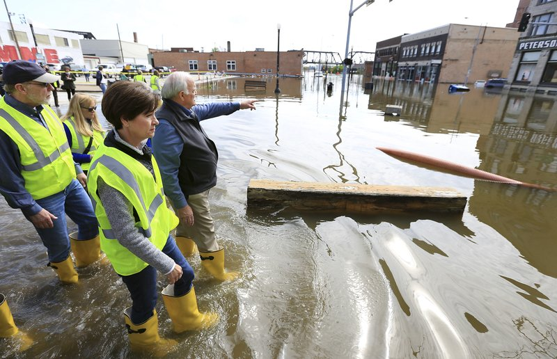 Davenport mayor Frank Klipsch points to the Peterson Paper Co. Apartments as he stops to talk with Iowa Gov. Kim Reynolds near the intersection of Pershing Ave. and E 2nd St. in downtown Davenport, Iowa during a tour of flooded areas of the community Friday, May 3, 2019. (Kevin E. Schmidt/Quad City Times via AP)