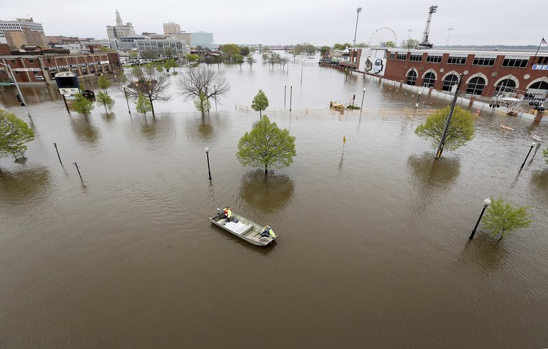 City of Davenport workers ferry sandbags across Mississippi River floodwaters to the Rivers Edge building, Thursday, May 2, 2019. The Mississippi River is expected to reach a record level of 22.7 feet Thursday night.  (Kevin E. Schmidt/Quad City Times via AP)