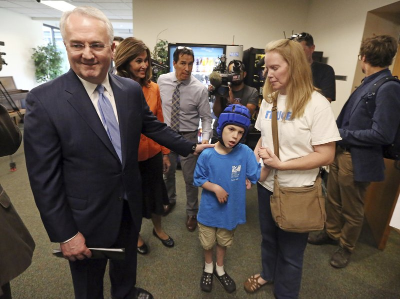 FILE - In this Aug. 23, 2018, file photo, Jack Gerard, left, a leader in The Church of Jesus Christ of Latter-day Saints, speaks with Heather Nelson and her son Matthew, 10, following a news conference with opponents of Utah's medical marijuana ballot initiative in Salt Lake City. Utah is asking a judge to dismiss a case filed by marijuana advocates claiming the state conspired with The Church of Jesus Christ of Latter-day Saints to overhaul a voter-approved medical pot ballot initiative. (AP Photo/Rick Bowmer, File)