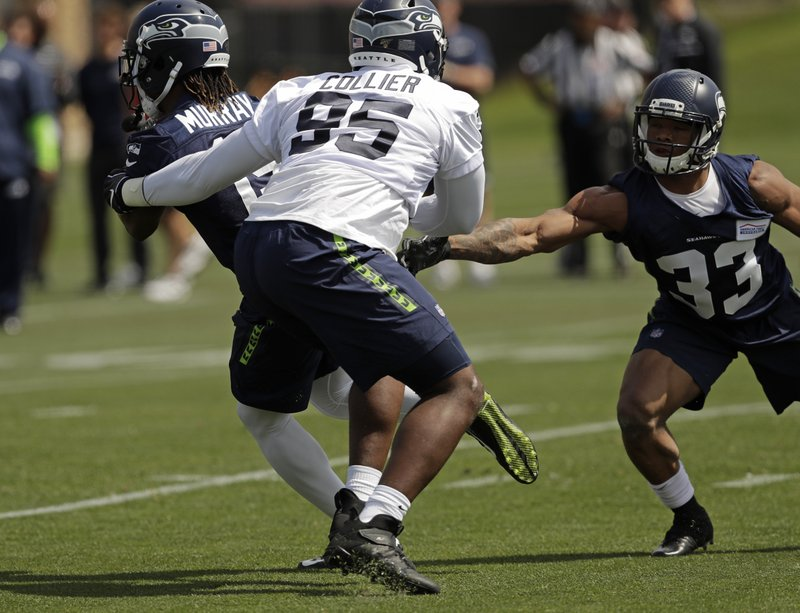 Seattle Seahawks defensive end L.J. Collier (95) tries to stop wide receiver Nyqwan Murray, left, as running back Marcelias Sutton (33) looks on during NFL football rookie minicamp, Friday, May 3, 2019, in Renton, Wash. (AP Photo/Ted S. Warren)