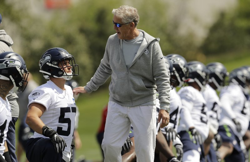Seattle Seahawks coach Pete Carroll, center, talks with rookie linebacker Cody Barton, left, during NFL football rookie minicamp Friday, May 3, 2019, in Renton, Wash. (AP Photo/Ted S. Warren)