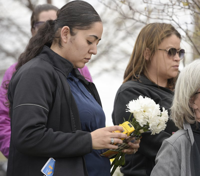 Luz Garcia of Rockford and Angelica Zamudio of Crystal Lake hold flower, toys and a teddy bear as they wait with other mourners to attend the visitation of 5 year old A.J. Freund of Crystal Lake at Davenport Family Funeral Home on Friday, May 3, 2019 in Crystal Lake, Ill. (Mark Black/Chicago Sun-Times via AP)