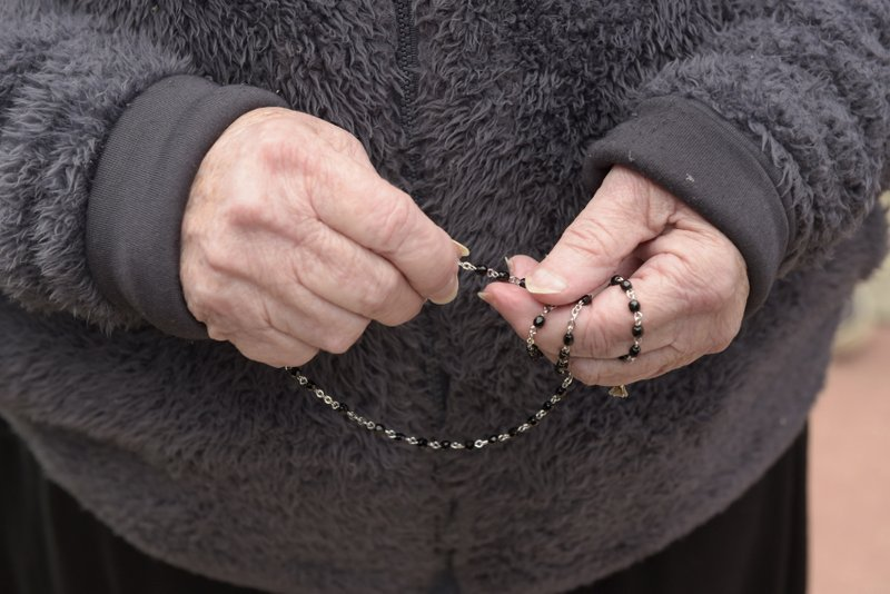 Mourner Gerri Noble, 75 of Crystal Lake prays the Rosary while waiting in line to attend the visitation of 5 year old A.J. Freund of Crystal Lake at Davenport Family Funeral Home on Friday, May 3, 2019 in Crystal Lake, Ill. (Mark Black/Chicago Sun-Times via AP)