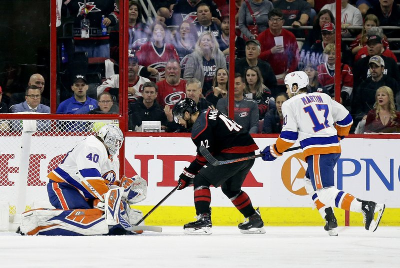 Carolina Hurricanes' Greg McKegg (42) scores against New York Islanders goalie Robin Lehner (40), of Sweden, during the second period of Game 4 of an NHL hockey second-round playoff series in Raleigh, N.C., Friday, May 3, 2019. Islanders' Matt Martin (17) looks on. (AP Photo/Gerry Broome)