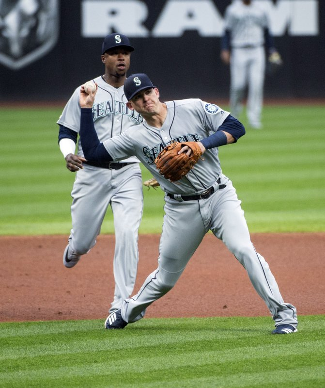 Seattle Mariners' Ryon Healy, front, throws out Cleveland Indians' Francisco Lindor as teammate Tim Beckham watches during the first inning of a baseball game in Cleveland, Friday, May 3, 2019. (AP Photo/Phil Long)
