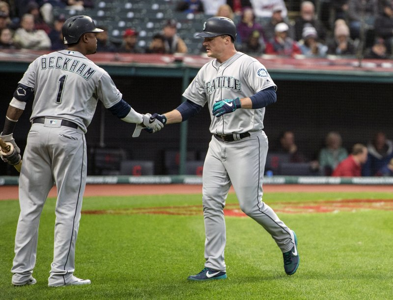 Seattle Mariners' Jay Bruce, right, is greeted by Tim Beckham after hitting a home run off Cleveland Indians starting pitcher Shane Bieber during the fourth inning of a baseball game in Cleveland, Friday, May 3, 2019. (AP Photo/Phil Long)