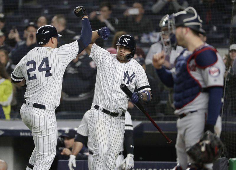New York Yankees' Gary Sanchez, left, celebrates with teammate Gleyber Torres, center, as Minnesota Twins catcher Mitch Garver looks away during the seventh inning of a baseball game Friday, May 3, 2019, in New York. (AP Photo/Frank Franklin II)