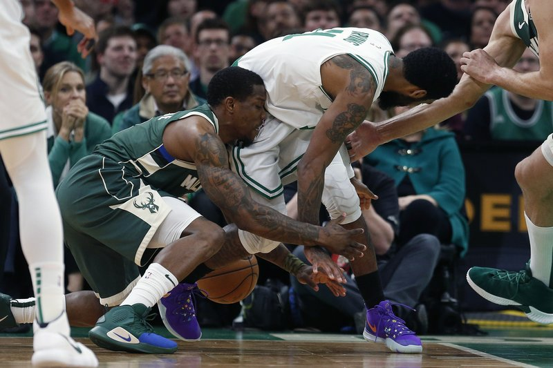 Milwaukee Bucks' Eric Bledsoe, left, and Boston Celtics' Kyrie Irving (11) vie a loose ball during the first half of Game 3 of a second-round NBA basketball playoff series in Boston, Friday, May 3, 2019. (AP Photo/Michael Dwyer)