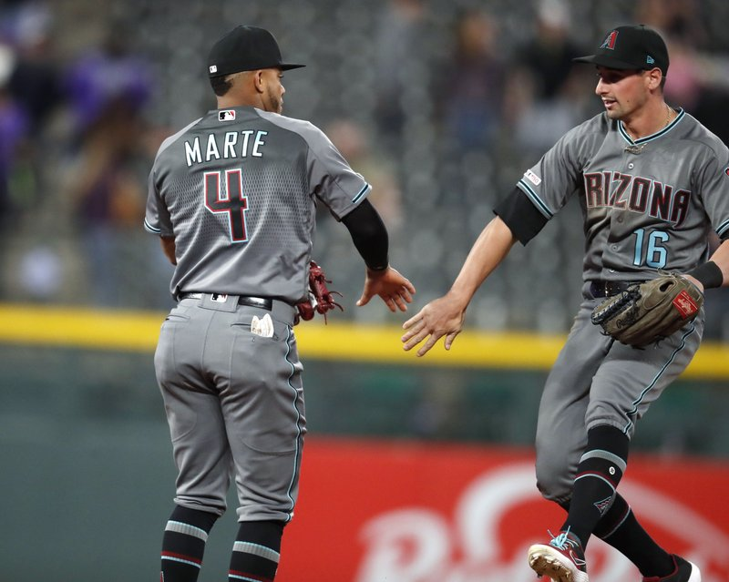 Arizona Diamondbacks second baseman Ketel Marte, left, celebrates with outfielder Tim Locator after the team's 10-9 win in a baseball game against the Colorado Rockies on Friday, May 3, 2019, in Denver. (AP Photo/David Zalubowski)