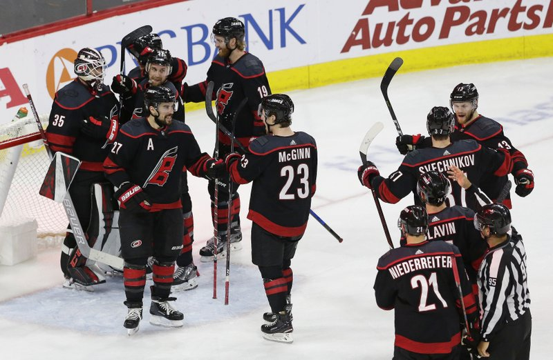 Carolina Hurricanes players celebrate following the team's win over the New York Islanders in Game 4 of an NHL hockey second-round playoff series in Raleigh, N.C., Friday, May 3, 2019. (AP Photo/Gerry Broome)