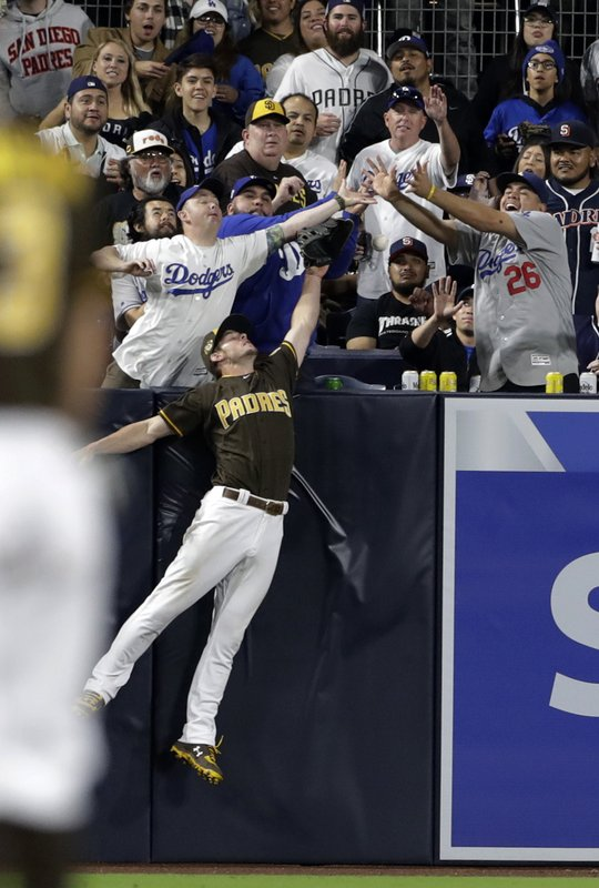 San Diego Padres center fielder Wil Myers can't reach a home run hit by Los Angeles Dodgers' Austin Barnes during the seventh inning of a baseball game Friday, May 3, 2019, in San Diego. (AP Photo/Gregory Bull)