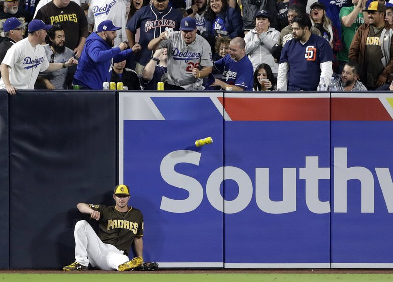 San Diego Padres center fielder Wil Myers sits on the warning track as a fan holds the ball after a home run by Los Angeles Dodgers' Austin Barnes and a beverage can falls, during the seventh inning of a baseball game Friday, May 3, 2019, in San Diego. (AP Photo/Gregory Bull)