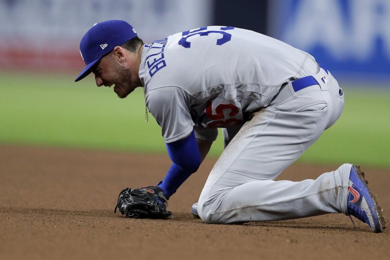 Los Angeles Dodgers first baseman Cody Bellinger reacts after straining his arm trying to field a ground ball hit for a single by San Diego Padres' Eric Hosmer during the fourth inning of a baseball game Friday, May 3, 2019, in San Diego. (AP Photo/Gregory Bull)