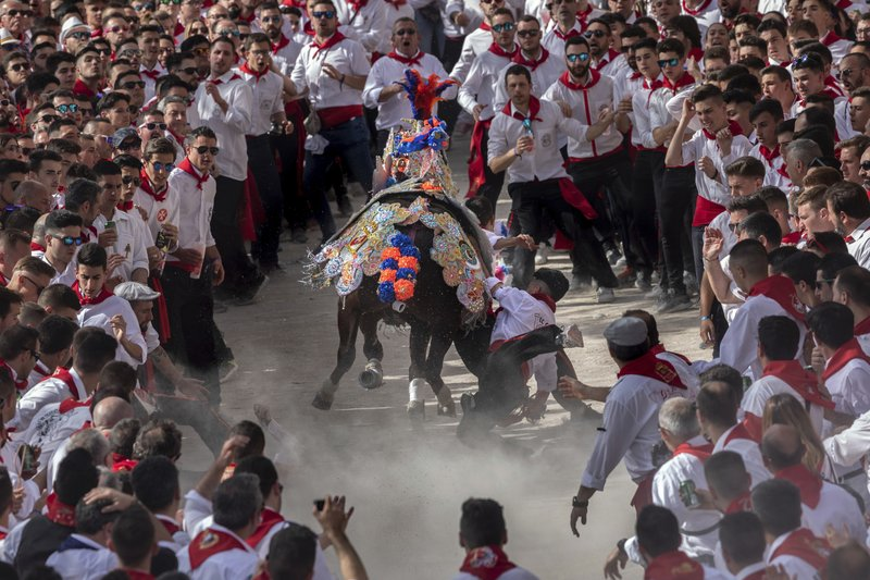 In this Thursday, May 2, 2019 photo, a troupe falls down while their horse make its way amid the crowd during the